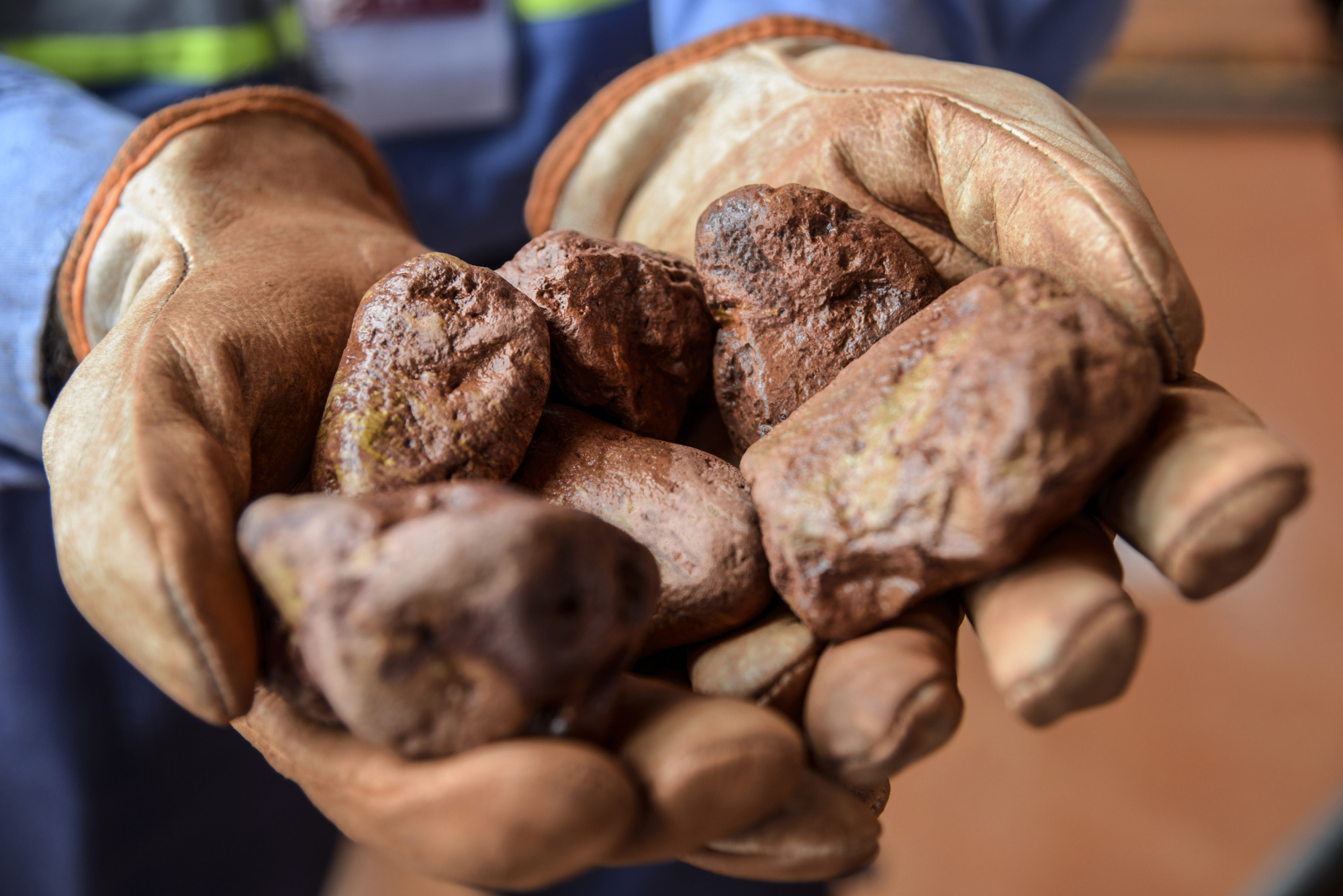 A worker displays cleaned bauxite stones for a photograph at the Paragominas bauxite mine, co-owned by Norsk Hydro and Vale SA, in Paragominas, Brazil, on Wednesday, April 13, 2016. Bauxite is extracted from the clay soil, crushed and transported via pipeline to Barcarena for refining and shipment to aluminium producers in Brazil and internationally. Photographer: Paulo Fridman/Bloomberg